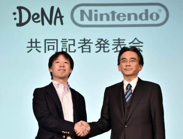 Japan's video game giant Nintendo president Satoru Iwata (R) shakes hands with Japanese online game operator DeNA president Isao Moriyasu during a press conference in Tokyo on March 17, 2015. Nintendo said on March 17 it was teaming up with a mobile gaming company to develop games for smartphones in what could be a turning point for the Japanese giant which has long refused to enter the soaring market.  AFP PHOTO / Yoshikazu TSUNO        (Photo credit should read YOSHIKAZU TSUNO/AFP/Getty Images)